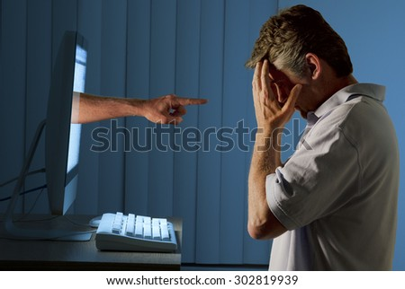 Severely distraught man sitting in front of a computer with a judgmental hand pointing at him from within the computer monitor showing being computer bullying bullied or stalked on social media. - stock photo