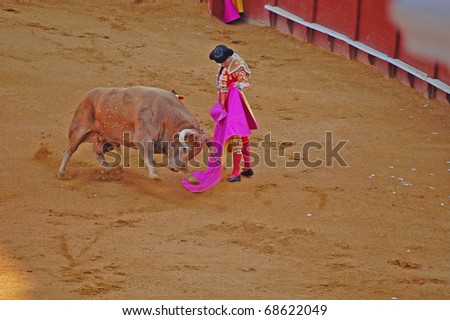 "SEVILLE - APRIL 30:  A bull charges Bullfighter David Fandila ""El Fandi"" during a fight for a sold out crowd at the Plaza de Toros de Sevilla April 30, 2009 in Seville, Spain. - stock photo"