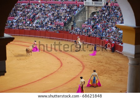 "SEVILLE - APRIL 30:  Bullfighter David Fandila ""El Fandi"" guides the bull toward the picador during a fight for a sold out crowd at the Plaza de Toros de Sevilla April 30, 2009 in Seville, Spain. - stock photo"