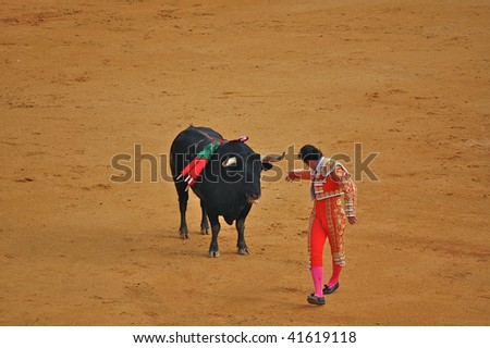 "SEVILLE - APRIL 30: Bullfighter David Fandila ""El Fandi"" steps away from the bull after planting the banderillas at the Plaza de Toros de Sevilla April 30, 2009 in Seville, Spain. - stock photo"