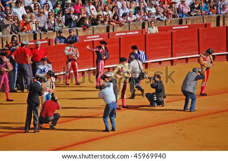 SEVILLE - APRIL 30:Photographers mod the bullfighters as they march into the ring at the at the Plaza de Toros de Sevilla April 30, 2009 in Seville, Spain. - stock photo