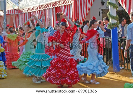 SEVILLE - APRIL 28: Young women in traditional flamenco dresses dance during the Feria de Abril on April 28, 2009 in Seville, Spain. - stock photo