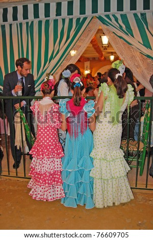 SEVILLE - APRIL 28: Young women in traditional flamenco dresses gather as the beautiful temporary neighborhood comes to life during the Feria de Abril on April 28, 2009 in Seville, Spain. - stock photo
