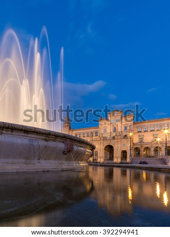 Seville City Landmark, Fountain and central building at Plaza de Espana Illuminated Building architecture exterior with Water Reflection at night in summer under clear blue sky, Spain - stock photo