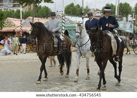 SEVILLE, SPAIN - APRIL 09, 2008: Men on horseback walk through the April Fair in Seville