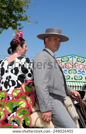 SEVILLE, SPAIN - APRIL 12, 2008 - Spanish couple in traditional dress sitting on a horse with Casitas to the rear at the Seville Fair, Seville, Andalusia, Spain, Western Europe, April 12, 2008. - stock photo
