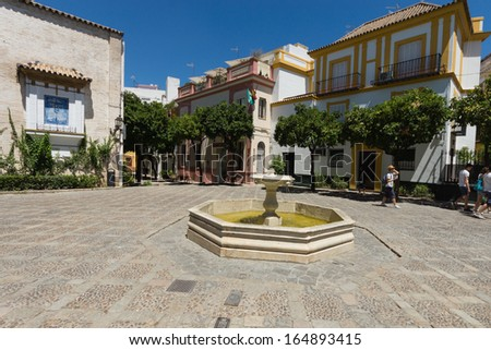 SEVILLE, SPAIN - AUG 08: Fountain in a typical Spanish small square in the center of Seville on August 08, 2013 in Seville, Spain. Seville is the capital of Andalusia. - stock photo