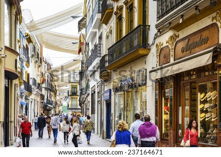 SEVILLE, SPAIN - CIRCA 2014: Shoppers stroll through Calle Sierpes. The street is considered the prime shopping district of the city. - stock photo