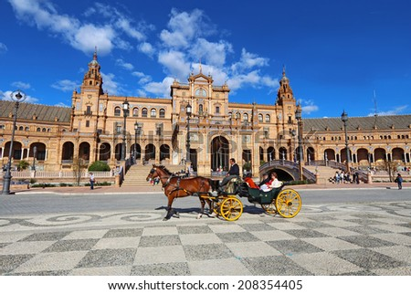 SEVILLE, SPAIN - MARCH 26 2014: Tourists and a horse-drawn carriage in front of the Plaza de Espana in Seville, Spain. The Plaza is a major tourist destination that was built in 1928. - stock photo