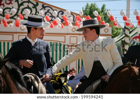 SEVILLE, SPAIN - MAY 2: Unidentified spanish riders chating on the horse at fairground stand in Seville fair, May 3, 2009 in Seville, Spain - stock photo