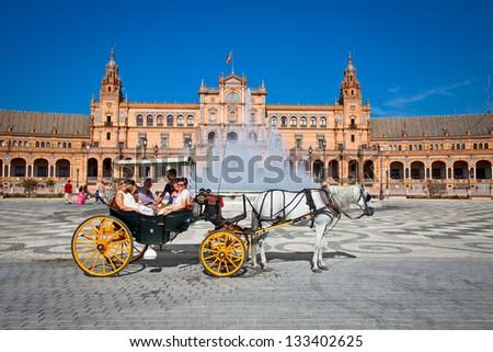 SEVILLE, SPAIN-SEP 10: Tourists enjoy a trip on horsedrawn cart on Plaza de Espana, Seville on Sep 10. 2011. - stock photo
