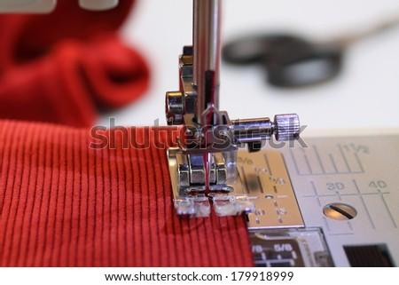 Sew velvet fabric on the sewing machine - stock photo