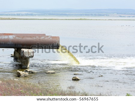 sewage from the sewer pollutes a lake - stock photo