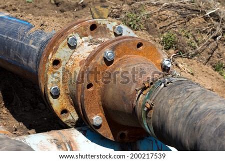 Sewage pumping station accident environmental man-made disaster. Repair broken old rusty pipes in open waste water flooded trenches - stock photo