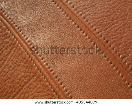 Sewed cowhide in high definition detail for textures or products. Two decorative seams and different texture. Hand made leather pad for horse riding in high quality. Natural lighting in winter. - stock photo