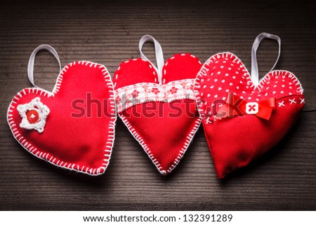 Sewed handmade red hearts on wooden background - stock photo