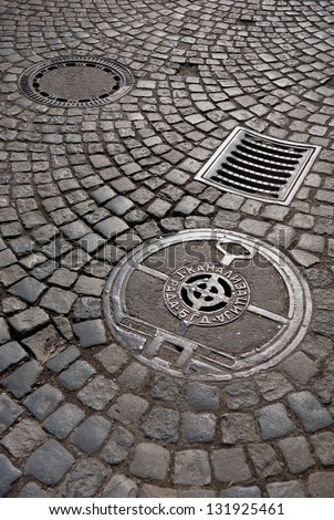 Sewer manhole cover and storm drain on cobblestone street. - stock photo
