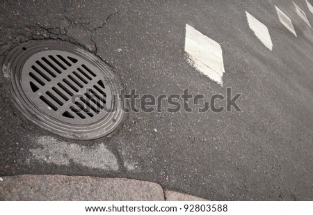 Sewer manhole on the asphalt road with white marking - stock photo