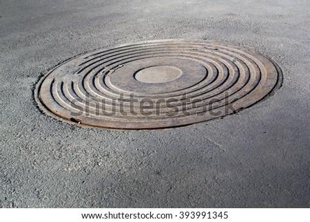 Sewer manhole on the city asphalt road - stock photo