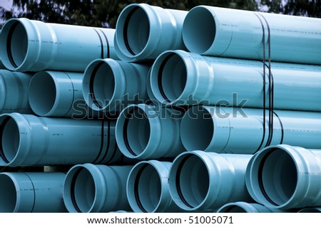 Sewer pipes waiting to be placed into the ditch at construction site. - stock photo