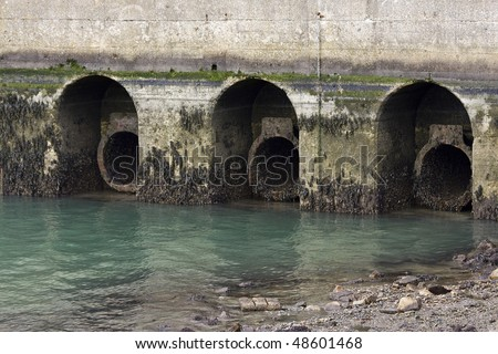 Sewerage pipes leading to the sea. - stock photo
