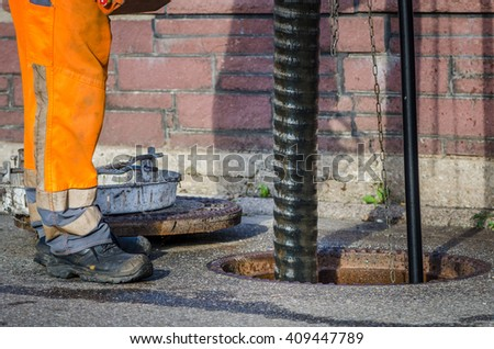 sewerage worker on street cleaning pipe - stock photo