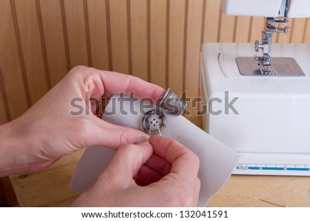 Sewing a button onto tan fabric with sewing machine in background - stock photo
