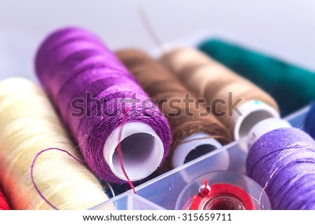 sewing accessories:  thread, bobbin, needle in plastic box close up with blurred background