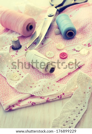 sewing accessories - thread, scissors, needles, buttons, ribbons on the fabric (vintage style) - stock photo