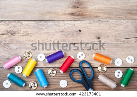 Sewing background with copy space. Colorful threads bobbins, scissors and buttons on old wooden table. Accessories for needlework. Top view - stock photo