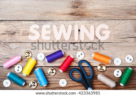 Sewing background with copy space. Colorful threads bobbins, word Sewing, scissors and buttons on old wooden table. Accessories for handmade. Top view - stock photo