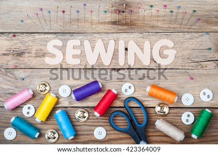 Sewing background with copy space. Colorful threads bobbins, word Sewing, scissors, pins and buttons on old wooden table. Accessories for handmade. Top view - stock photo