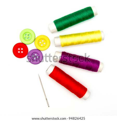sewing buttons and needle with thread isolated on white