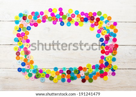 Sewing buttons on a wooden background with copy space. Colorful frame - stock photo