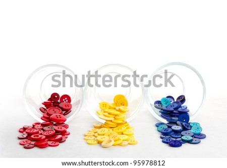 Sewing buttons spilling from jars in primary colors, red yellow and blue