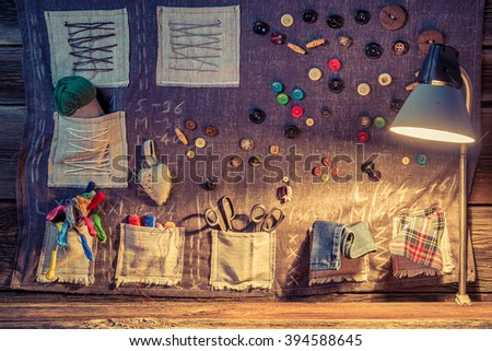 Sewing cloth with scissors, threads and needles in tailor workshop - stock photo