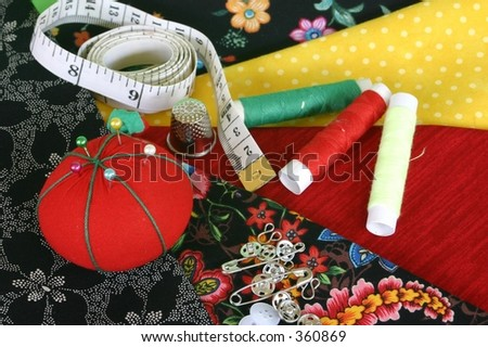 Sewing fabric with pincushion, tape measure, thimble, threads and fasteners