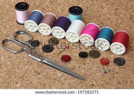 Sewing items: buttons, material, measuring tape, bobbins, buttons, cloth, safety pins, needles, spools of thread,  scissors - stock photo
