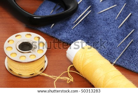 Sewing items on a brown table - stock photo