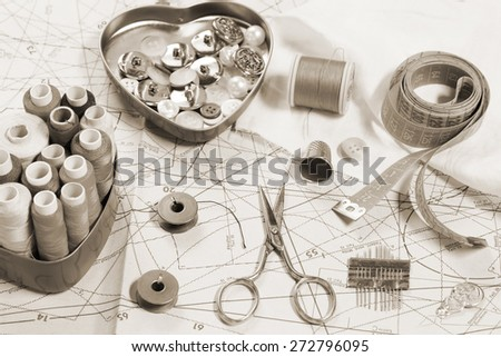 Sewing items on a sewing pattern - toned image - stock photo