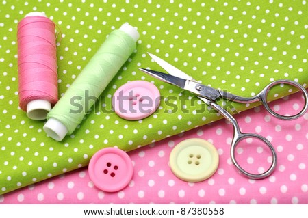 Sewing items on colorful fabrics - stock photo