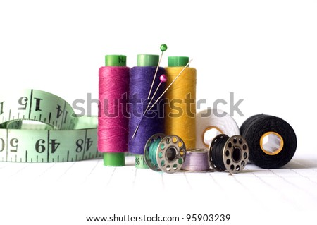 sewing kit, needles, thread and measuring tape isolated on a white background - stock photo