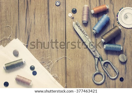 Sewing kit. Scissors, bobbins with thread and needles on the old wooden background - stock photo