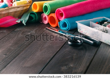 Sewing kit. Scissors, bobbins with thread, buttons and needles on rustic wooden table - stock photo