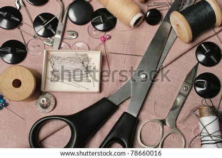 Sewing kit. Tailoring tools. Scissors, bobbins with thread, buttons and needles on the pink threaded fabric. - stock photo
