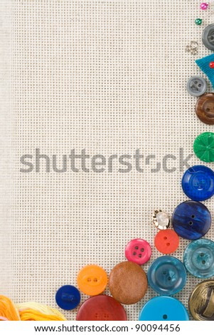 sewing kit with buttons and needles on cottons background - stock photo