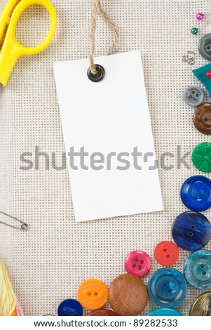 sewing kit with buttons, scissors and needles on cottons background - stock photo