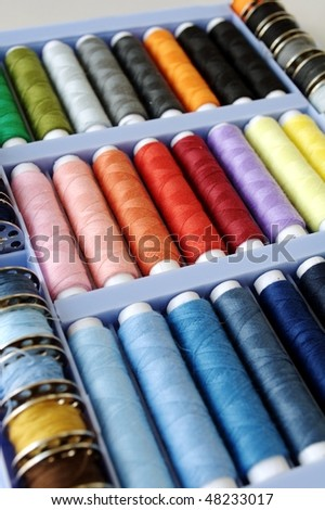 Sewing kit with colored spools of threads - stock photo