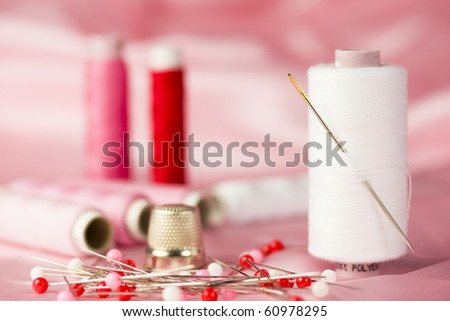 Sewing kit with cottons, pins and thimble in red and white - pink background. - stock photo