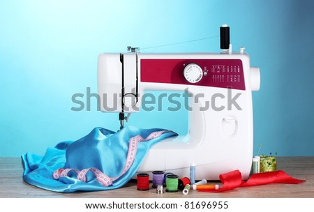 sewing machine and fabric on blue background - stock photo